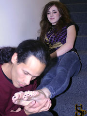 She has James take off her boots, sits down on the stairs and proceeds to verbally humiliate James as he kisses her feet.