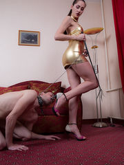 Slender young brunette is spanking her slave with whip and making him to suck her heels and lick her feet